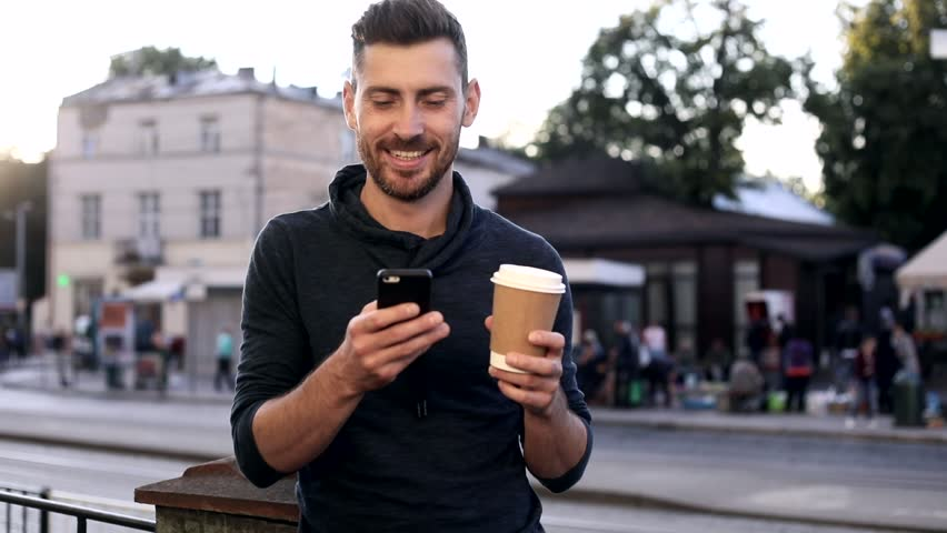 Close up of Handsome Man Standing in the Town. Holding a Paper Cup with Black Coffee. Using her Modern Smartphone. Reading a Message. Crowded Bus Stop on the Background.