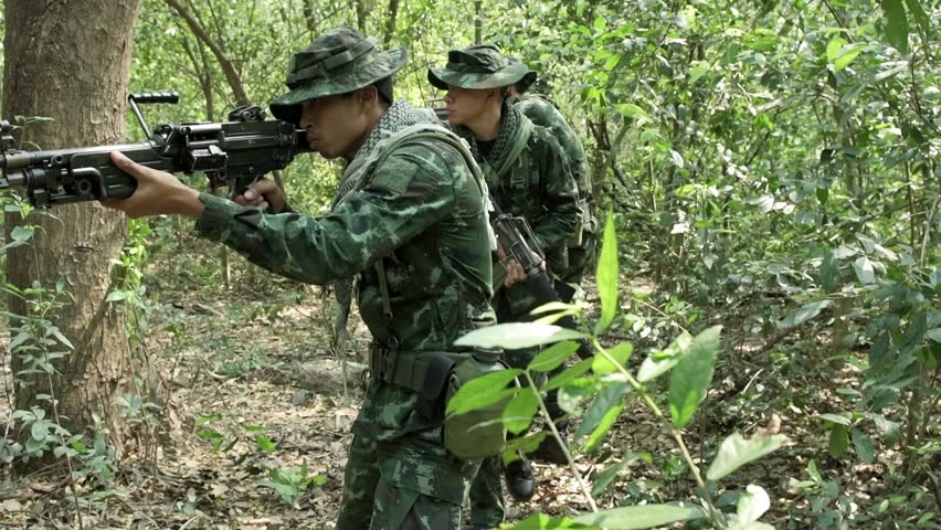 Soldiers walking and patrolling, ready to fire. Chinese army soldiers with green camouflage uniform in high grass tropical jungle walking. Modern warfare and combat concept.  | Shutterstock HD Video #1013886278