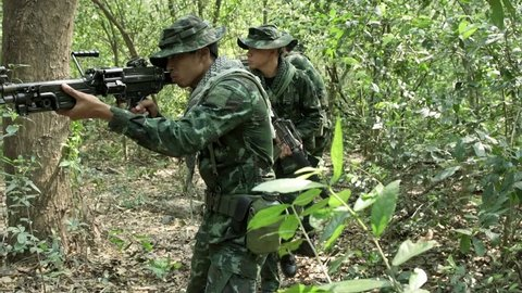 Soldiers walking and patrolling, ready to fire. Chinese army soldiers with green camouflage uniform in high grass tropical jungle walking. Modern warfare and combat concept.