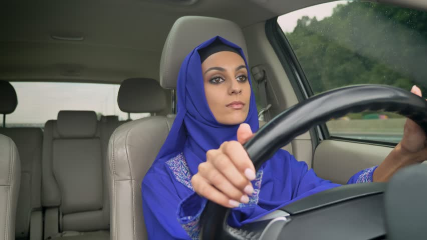 Young pretty muslim woman in hijab driving a car on the road, smiling