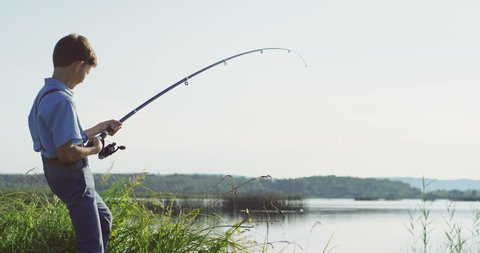 Small Caucasian boy fisherman catching a fish on a rod and getting it out on the lake. Outdoors.