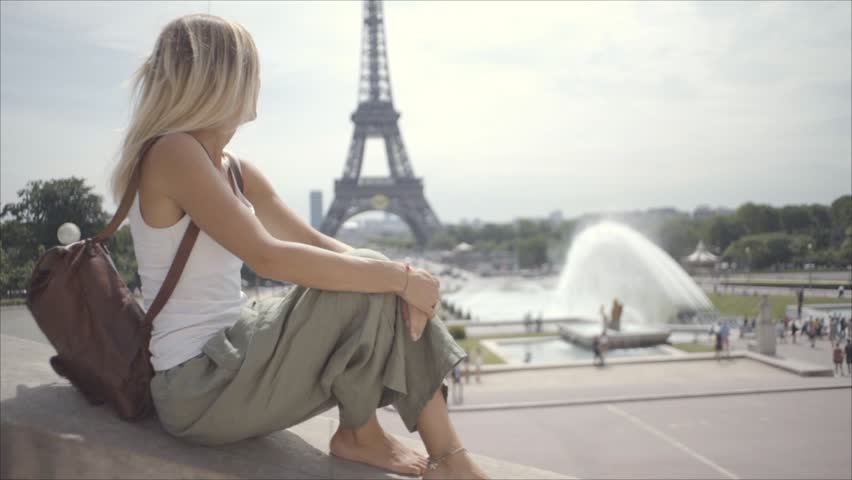 Real people travelling, woman sitting by stairs looking out at the Eiffel Tower in Paris, France. Slow motion  | Shutterstock HD Video #1013901818