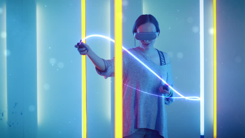 Beautiful Young Girl Wearing Virtual Reality Headset Draws Abstract Lines and Figures with Joysticks. Creative Young Girl Does Concept Art with Augmented Reality.  Shot on RED EPIC-W 8K Helium Camera.