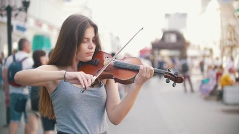 Young woman playing a violin at the pedestrian street