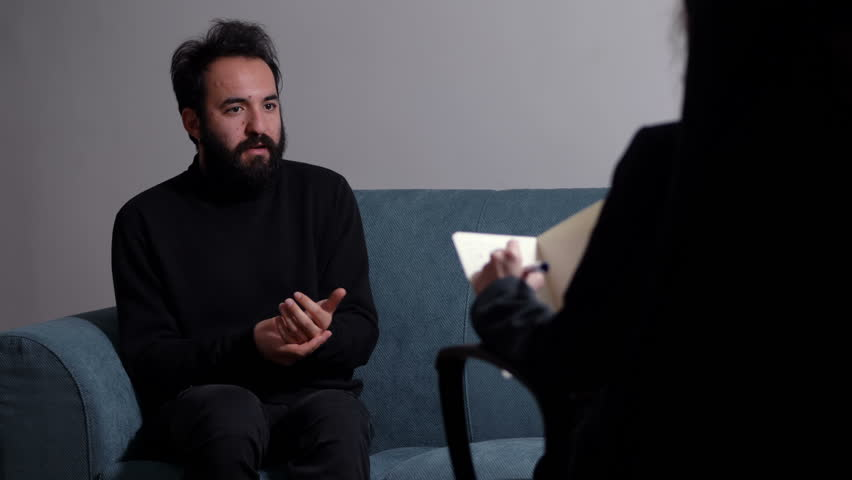 Nervous man sitting during therapy at the psychologist- anxiety, stress,panic | Shutterstock HD Video #1013917388