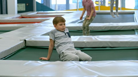 Tracking shot of tired little boy of primary school age resting on trampoline while two other children jumping in the background