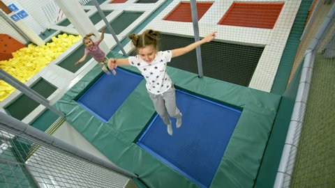 High angle view of two adorable schoolgirls jumping and bouncing on trampoline in indoor amusement park