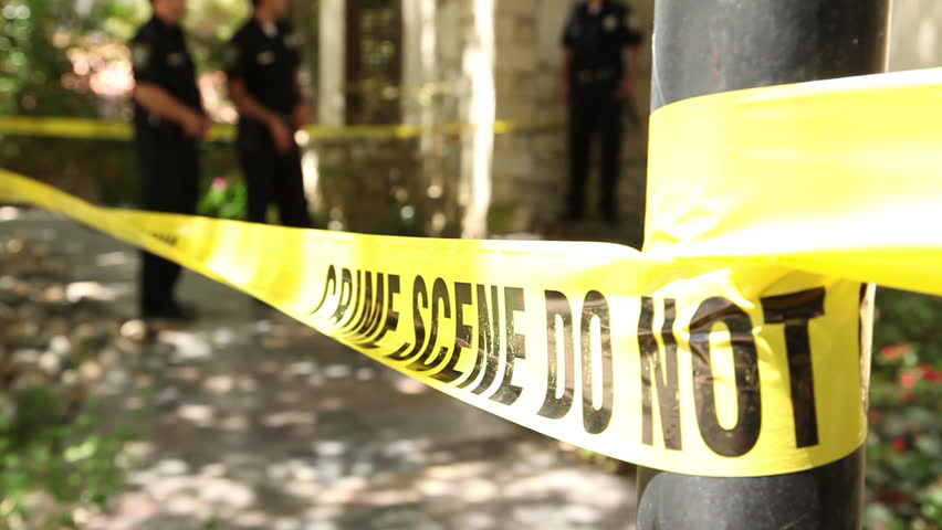 Closeup shot of police tape at a crime scene, with cops guarding the perimeter of a home in the background as a detective enters and exits through the scene.