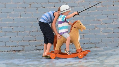 Amusing child rolling his younger brother on toy rocking horse with plastic sword. Boy dreams of battles, victories and adventures.Concept of moral education, patriotism, hero, super. Children happy
