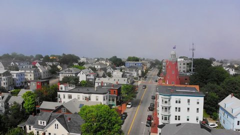 A foggy daytime reverse aerial view of the business district along Congress Street in Portland, Maine. The Portland Observatory is seen in the distance.