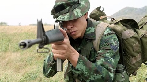 Slow motion of  soldier aiming his weapon. Standing up aiming their assault rifle down range. Portrait close up shot. Digital green camo.