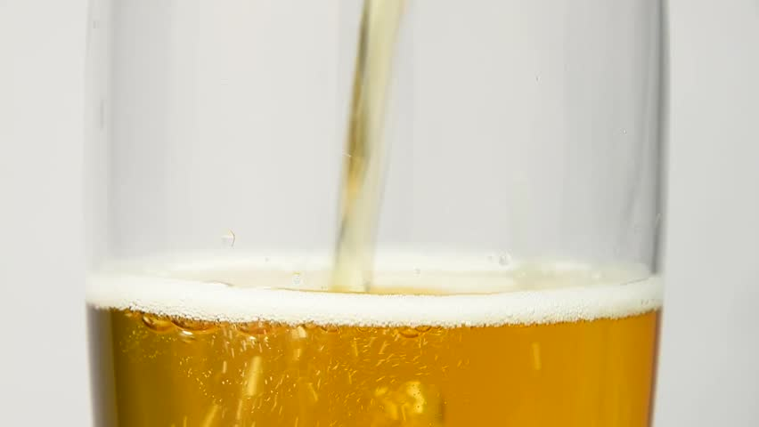 Close up background of pouring beer with bubbles and foam in glass, low angle side view, slow motion | Shutterstock HD Video #1013996288