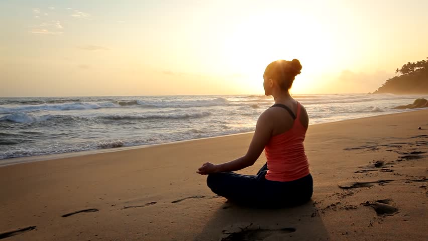 Woman doing yoga - meditate and relax in Padmasana Lotus asana pose with chin mudra outdoors at tropical beach on sunset | Shutterstock HD Video #1014000668
