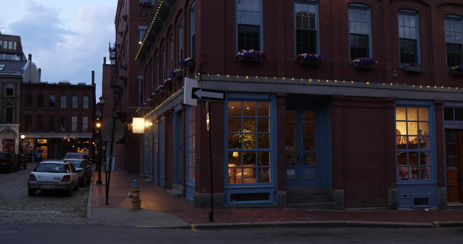 An evening exterior establishing shot of a New England city's corner red brick gift shop.