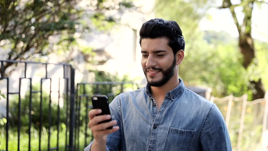Close up view of Handsome Young Man Using his Mobile Device. Walking up the Street in the Town. Private Houses around him. Stylish Hairstyle. Man Wearing Casual Jeans Shirt. Great Mood. | Shutterstock HD Video #1014007148