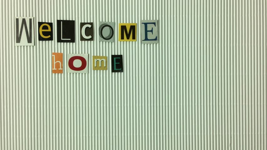 "Letters cut with the phrase ""Welcome home moving on white background. 