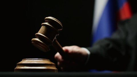 Judge with gavel in his hand hammering against Russian flag and black background in courtroom