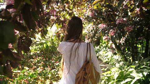 Following a beautiful woman walking between tropical trees blossoming. Location Balata garden Martinique. Sunny day