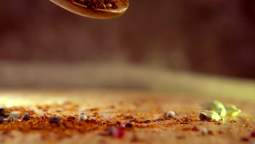 Spices falling from wooden spoon. Pepper, paprika, seasonings close-up.  Cooking concept, flavour. Various Indian Spices and herbs over brown background. Slow motion 4K UHD video