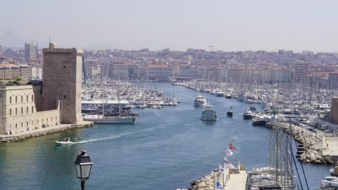 Timelapse of Vieux-Port de Marseille at harbor entrance. Famous old port in France now marina for boats and ferries. Historic landmarks in classical European maritime town.