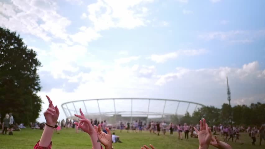 Group of friends at summer festival sitting on grass enjoying music, slow motion | Shutterstock HD Video #1014085838