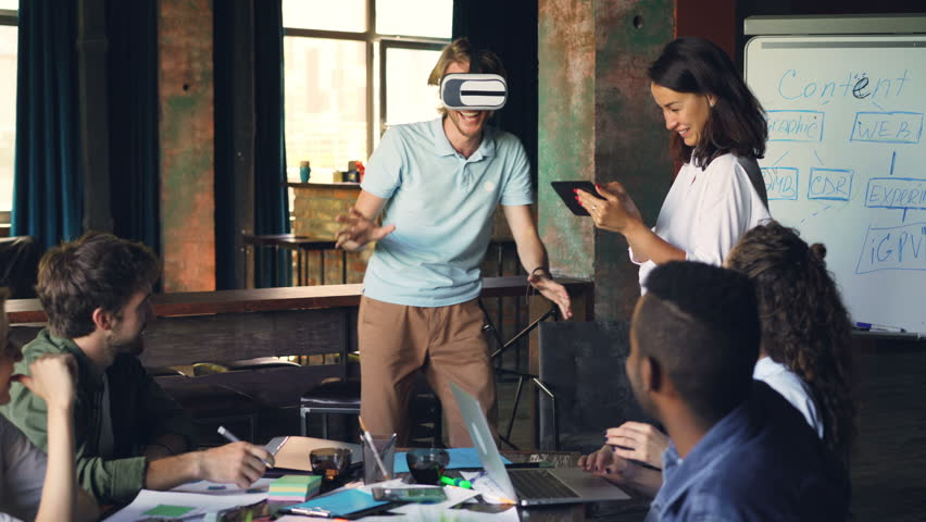 Young man wearing virtual reality glasses is having fun playing game while his colleagues are looking at him, laughing and using laptop and tablet in office. | Shutterstock HD Video #1014103538