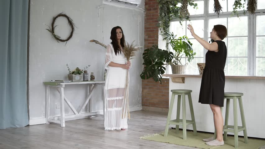 Beautiful pregnant woman with bouquet in white peignoir posing for female photographer. The photographer explains how to make a perfect pose