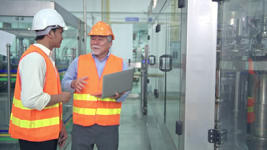 Senior quality inspector teaching junior team member in factory. Chinese old male with his young team discussing quality issue with bottle production line in background. | Shutterstock HD Video #1014124808