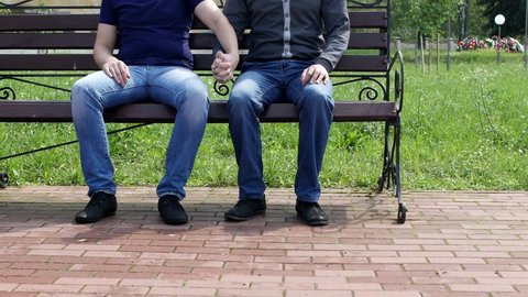 a man sits on a bench in the city to him another man approaches, they stroke one another on the leg, take hands and leave, gays, homosexuality
