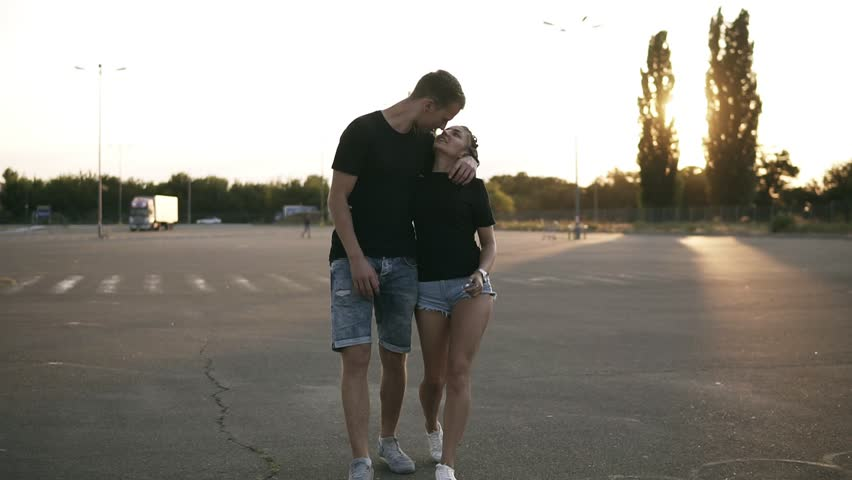 Portrait of a young stylish couple walking by shop parking and holding hands. Happy, loving couple outdoors. Both wearing denim shirts and black T shirts. Evening, sunset | Shutterstock HD Video #1014138578