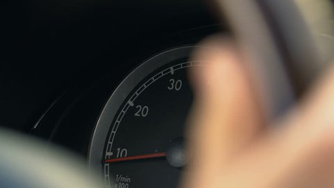 Person driving car, turning steering wheel, view on speedometer, close-up
