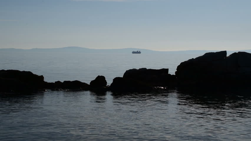 Silhouettes of rocks rising from the sea and cruiser ship in the background   Shutterstock HD Video #1014146558