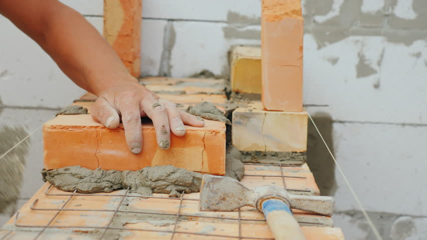 A professional worker puts the brick in the brickwork