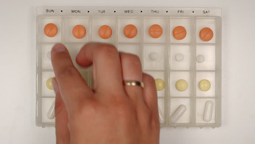 TOP VIEW: Female hand takes a pill from a pill organizer