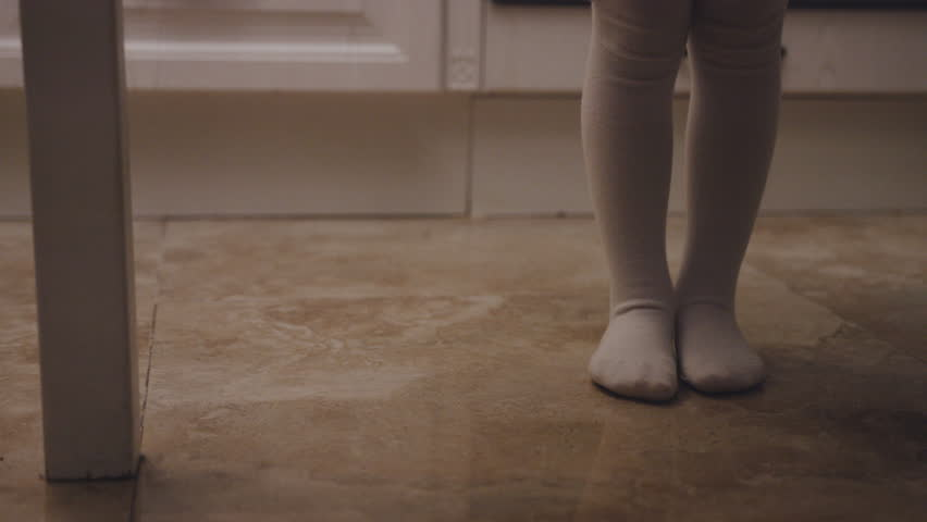 Close up of the kid's barefeet in white tights standing in the kitchen and kitchen stuff falling on the floor. Indoors