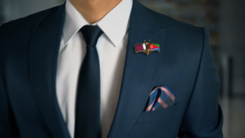Businessman Walking Towards Camera With Friend Country Flags Pin Qatar - Eritrea