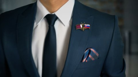 Businessman Walking Towards Camera With Friend Country Flags Pin Qatar - Slovakia