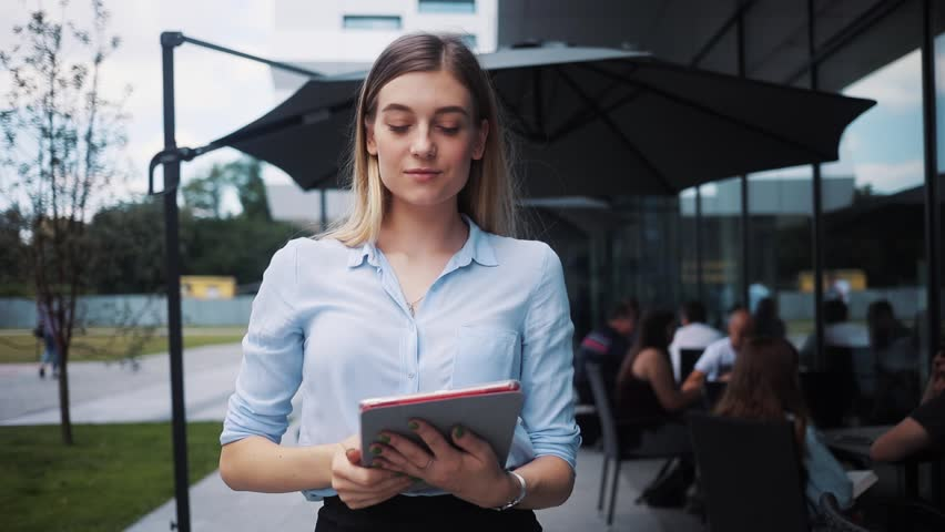 Happy beautiful business lady uses tablet computer walk near business center smile attractive technology girl internet young digital work screen smart one student touch professional holding looking | Shutterstock HD Video #1014212828
