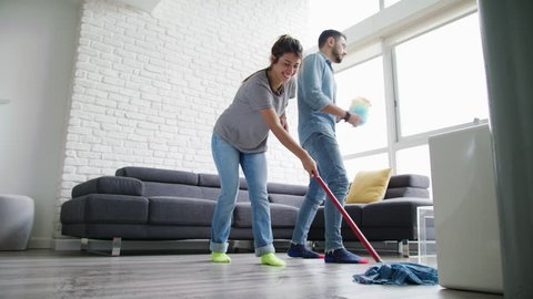 Young couple doing housework and chores. Man and girlfriend wipes the floor with mop and singing. Concept of teamwork and fun when doing housekeeping tasks.