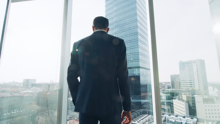Thoughtful Businessman Wearing Suit Standing in His Office, Looking out of the Window and Contemplating Next Big Business Contract. Shot on RED EPIC-W 8K Helium Cinema Camera. | Shutterstock HD Video #1014231668
