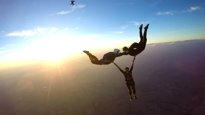 Skydivers having fun at the amazing sunset 4K video | Shutterstock HD Video #1014253508