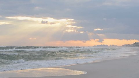 Dreamy pink pastel orange sunset in Santa Rosa Beach, Florida with Pensacola coastline coast cityscape skyline in panhandle with ocean gulf of mexico waves on shore, reflection in slow motion