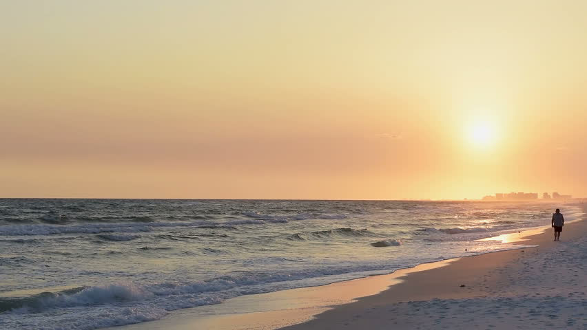 Sunset in Santa Rosa Beach, Florida with Pensacola coastline coast cityscape skyline, one man walking, in panhandle with ocean gulf of mexico waves, reflection in slow motion