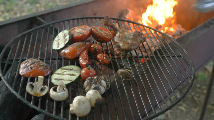 The chef takes the last piece of meat with tongs and takes the vegetables on the grill, zucchini, tomatoes, mushrooms, garlic head, the chef turns the grilled vegetables with forceps, the fire seeps | Shutterstock HD Video #1014294698