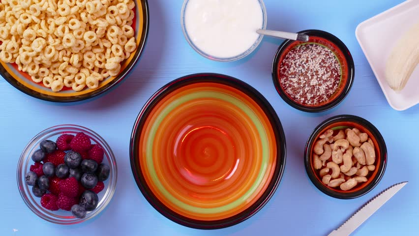 Cornflakes with natural yogurt, mix of fresh strawberries, raspberries, blueberries, chia seeds, cashew nut, banana for delicious breakfast or dessert. Healthy eating concept in stop motion animation | Shutterstock HD Video #1014298688