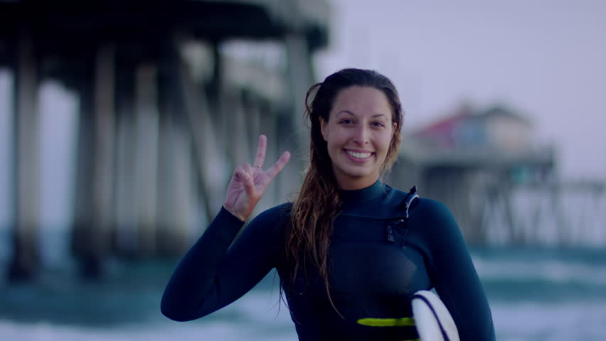 Portrait Of Surfer, She Smiles And Holds Up A Peace Sign At Sunset Next To Huntington Beach Pier, CA, USA (Slow Motion)