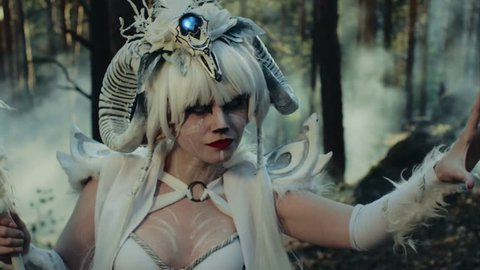Forest deity faun is standing alone in a woodland. Woman with horns and scary artistic makeup, looking by white eyes and conjuring
