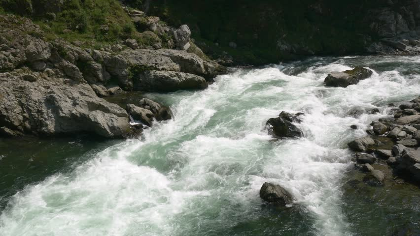 Person in forground while six rafters go down the whitewater in the background on the Yoshino River in Tokushima Japan