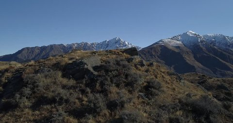 Aerial reveal of small mountain village (Queenstown) from behind a mountain