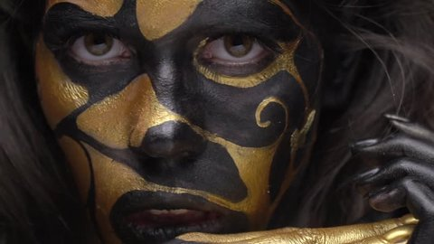 Brunette in black and gold make-up pulls her lip and looks at the camera, close up